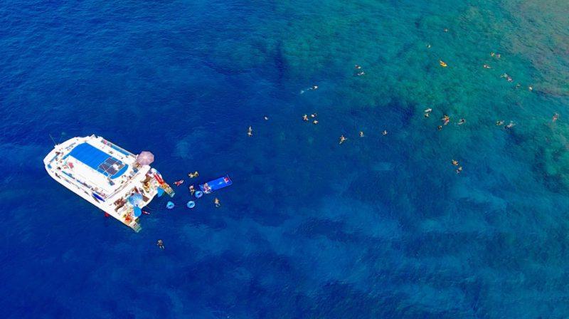 people in water snorkeling next to catamaran