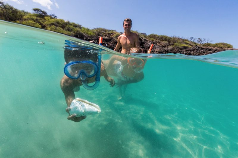 Child finds shell while snorkeling at Hapuna