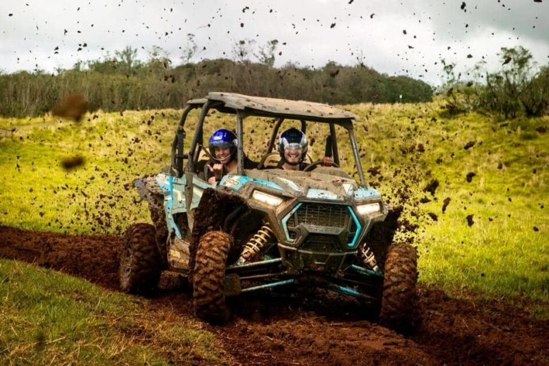 2 people in ATV getting muddy