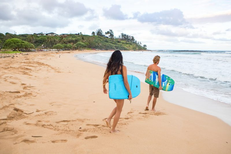 Couple head out to bodyboard in Kealia, Kauai