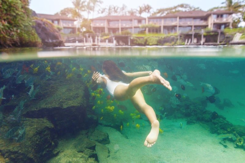 Woman swimming underwater with fish at King's Pond (Four Seasons Hualalai on the Big Island)
