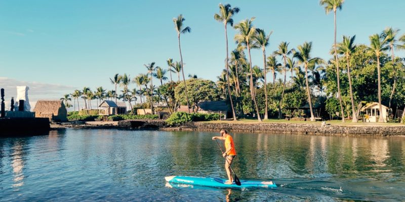 a stand-up paddle boarder is heading out into Kailua Bay.