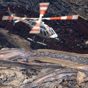 helicopter flies over red hot lava