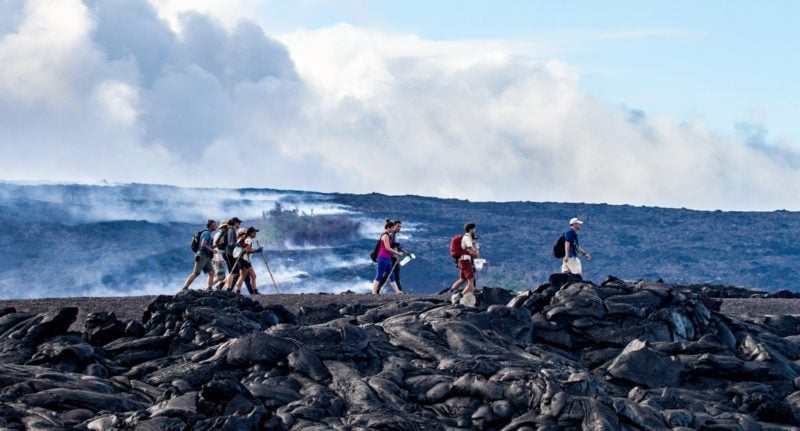 tour group hiking over lava
